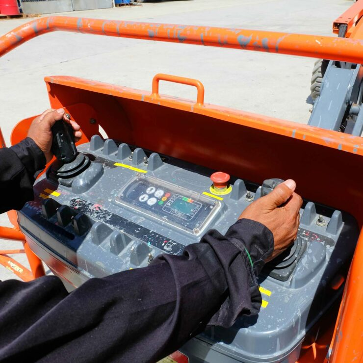 Close up of a workers hands operating machinery controls