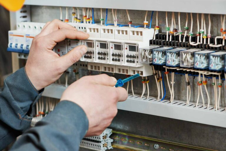 Electrician's hands tightening electric actuator equipment in fuse box